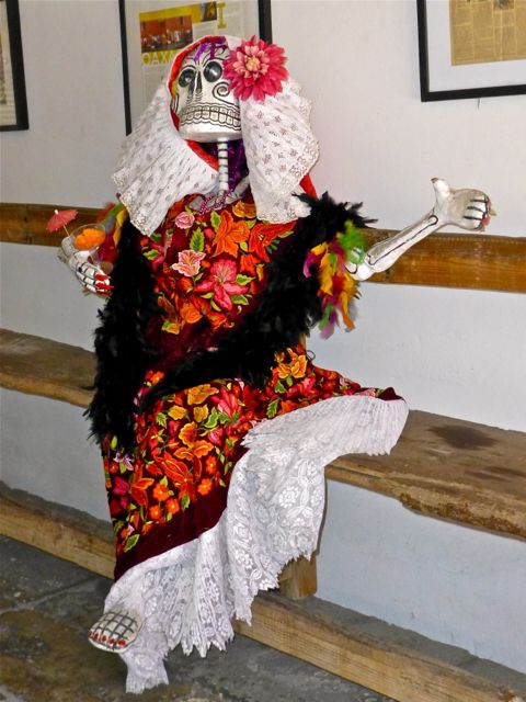 Seated Catrina in Tehuana traje holding cocktail glass with umbrellas.