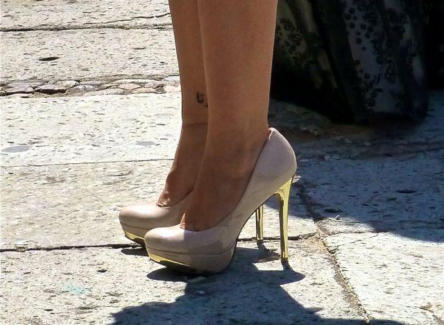 lower legs of woman wearing 4+ inch high heels