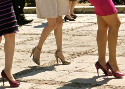 Lower legs and feet of 3 women wearing high heels