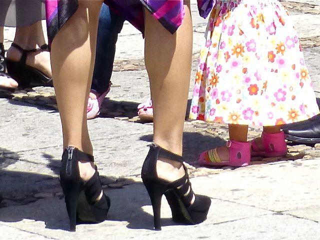 """Lower legs of a woman wearing black high (4"""") heels."""