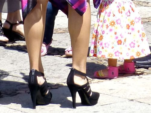 "Lower legs of a woman wearing black high (4"") heels."