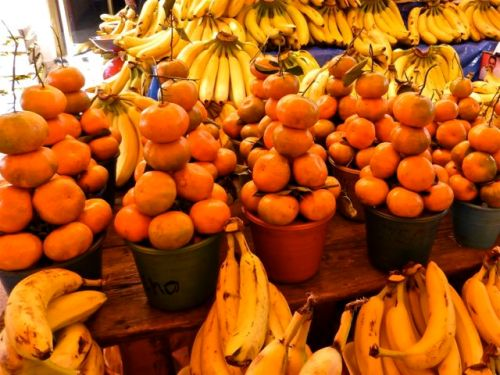 mounds of bananas and tangerines
