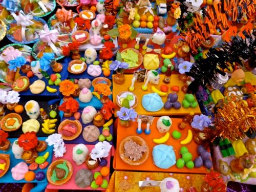 Tiny tables with miniature clay foods and beverages
