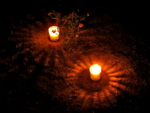 Night shot of two lighted votive candles casting halos on the ground