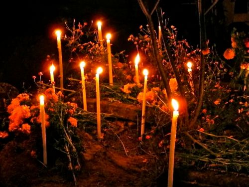 Night shot of tall lighted candles perched around and on graves.