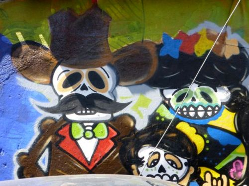Colorful wall mural of skeleton with mustache with female skeleton