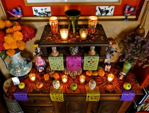Day of Dead home altar with fruit, candles, bread, calaveras, sugar skulls, etc.