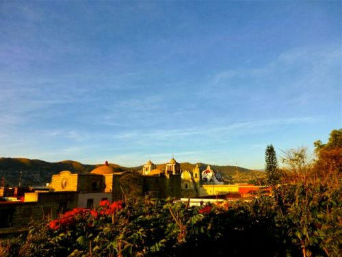 Blue sky, African tulip trees in foreground, churches in mid-ground, mountains in distance.