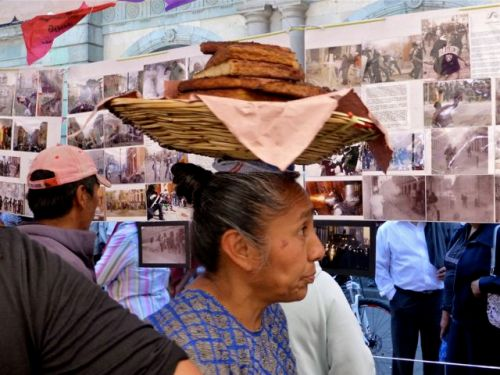 Women looking at photos, with a basket of sliced bread on her head.