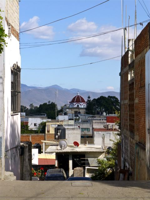 Looking down street, red domed church mid ground, mountains in distance