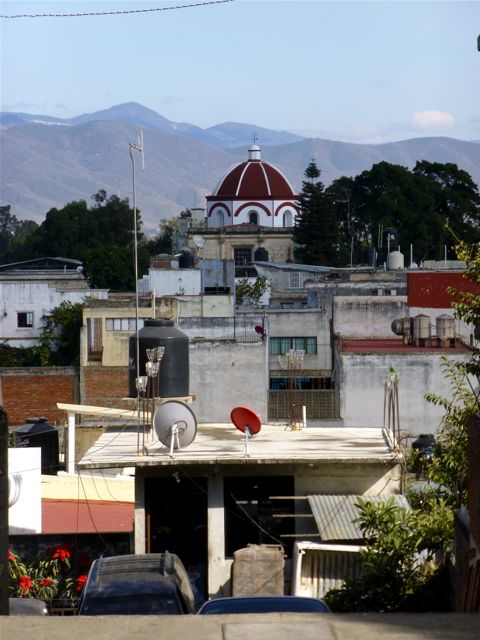 Looking over rooftops at red domed church in mid distance and mountains in background