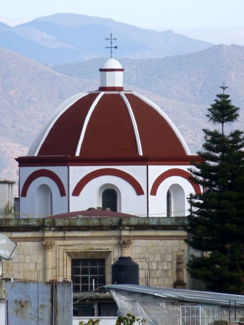 Red dome of church in foreground with mountains in background