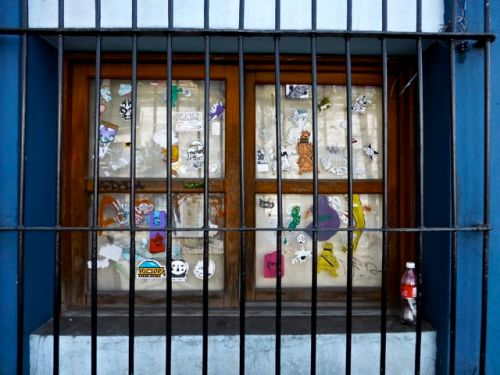Stickers on window panes behind iron grating