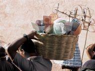 Shouldering a basket of offerings