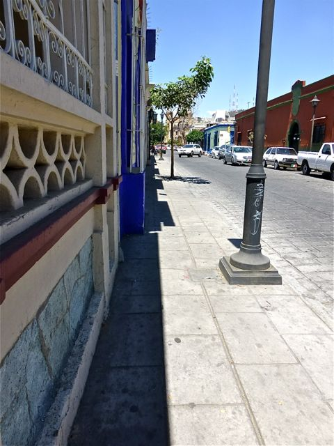 Empty sidewalk with sliver of shade
