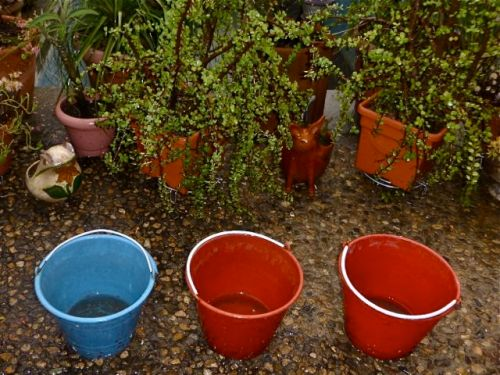 Wet patio with water in buckets