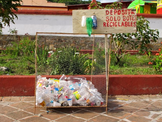 """Sign """"deposita solo botes reciclables"""" and basket 1/3 filled with plastic bottles underneath"""