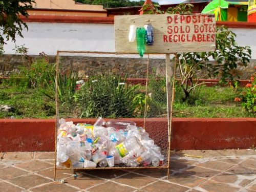 "Sign ""deposita solo botes reciclables"" and basket 1/3 filled with plastic bottles underneath"