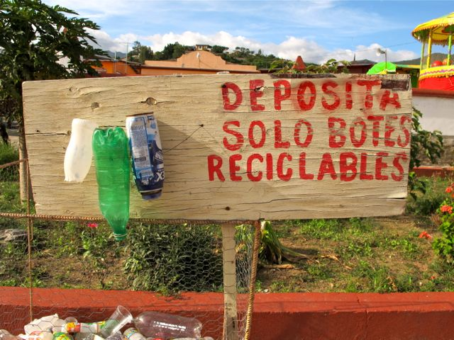 """Sign """"deposita solo botes reciclables with 3 plastic bottles nailed to it"""
