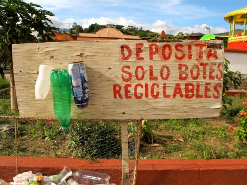 "Sign ""deposita solo botes reciclables with 3 plastic bottles nailed to it"