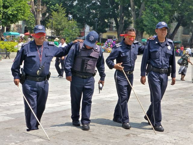 Blindfolded police walking with white canes