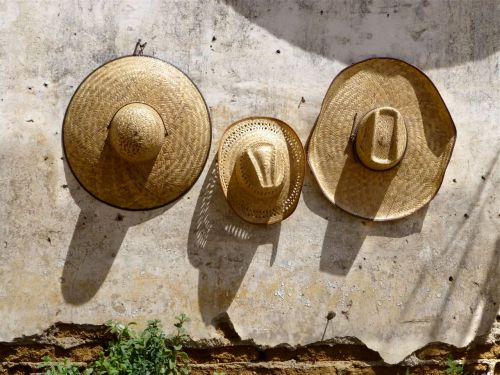 3 straw hats on concrete wall