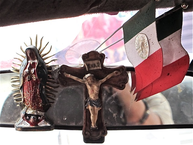 Virgin of Guadalupe, crucifix, 2 Mexican flags on rear view mirror