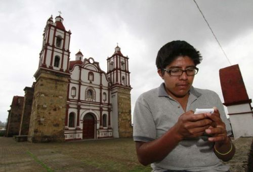 A local resident uses his mobile phone in Talea de Castro, Oaxaca State, Mexico, on August 17, 2013. For considering it to be slightly profitable, the big companies of mobile telephony refused for years to give its services in Talea, but the population -- mostly of indigenous origin -- adopted a novel system and created its own company, the Red Celular de Talea (RCT) (Talea Mobile Network).