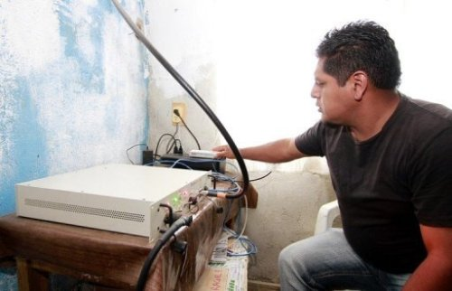 A local resident operates the equipment enabling mobile communications in Talea de Castro, Oaxaca State, Mexico, on August 17, 2013.