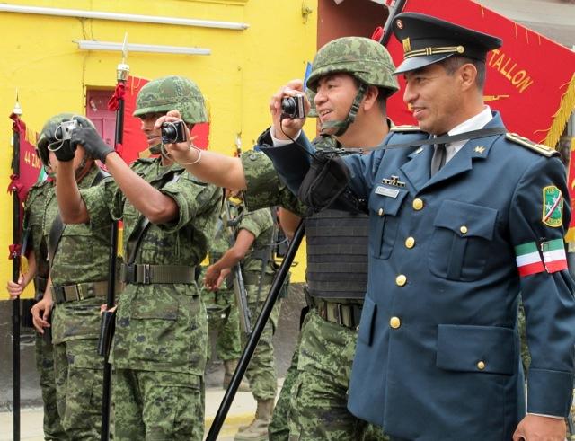 Men in military uniforms taking photos