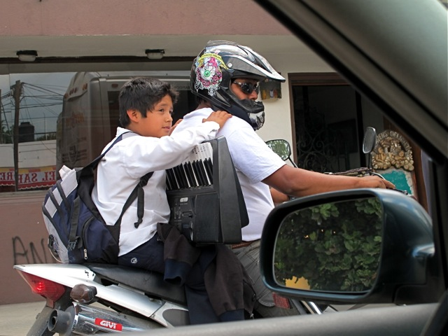 Boy on motorcycle holding keyboard