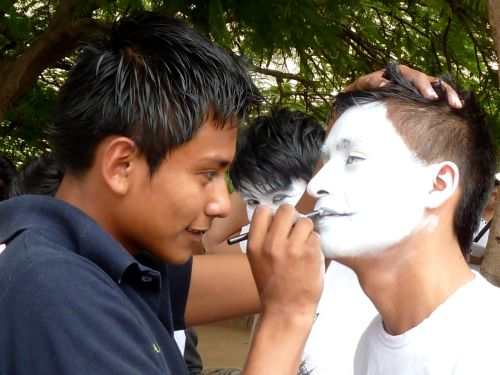 Young man painting face of another young man