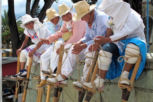 5 stilt dancers sitting on a ledge.