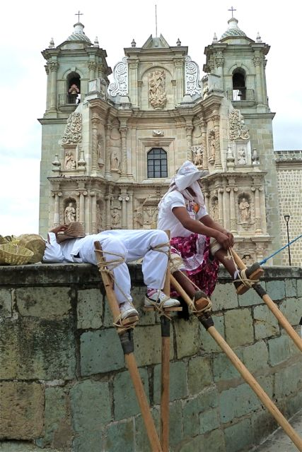 Stilt dancers sitting on ledge, Basilica of Soledad in background