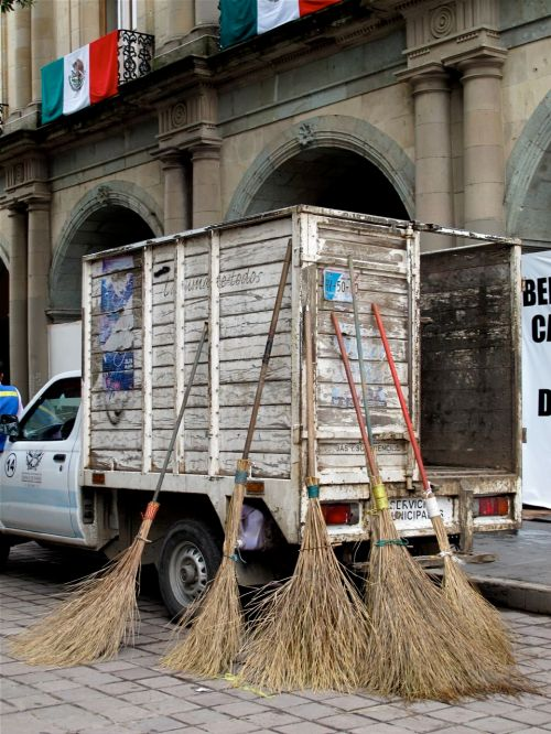 5 brooms leaning against truck