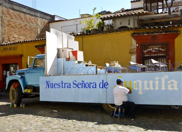 Man painting a banner on a flatbed truck
