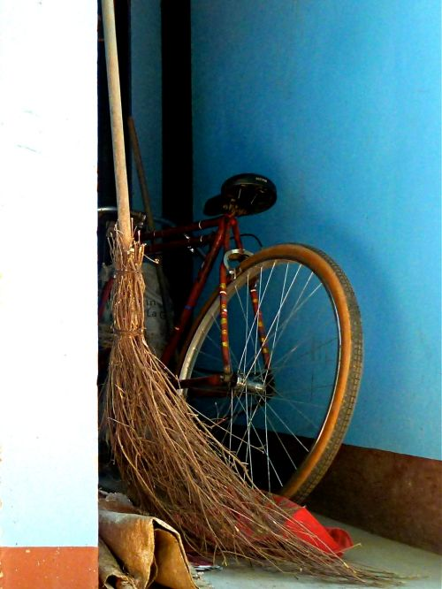 Broom leaning against wall with bicycle