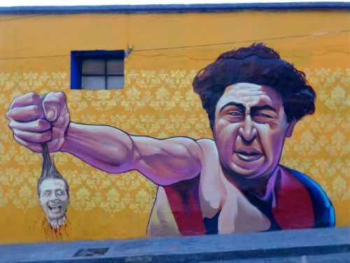 Mural on wall of giant man holding small Peña Nieto head by his hair
