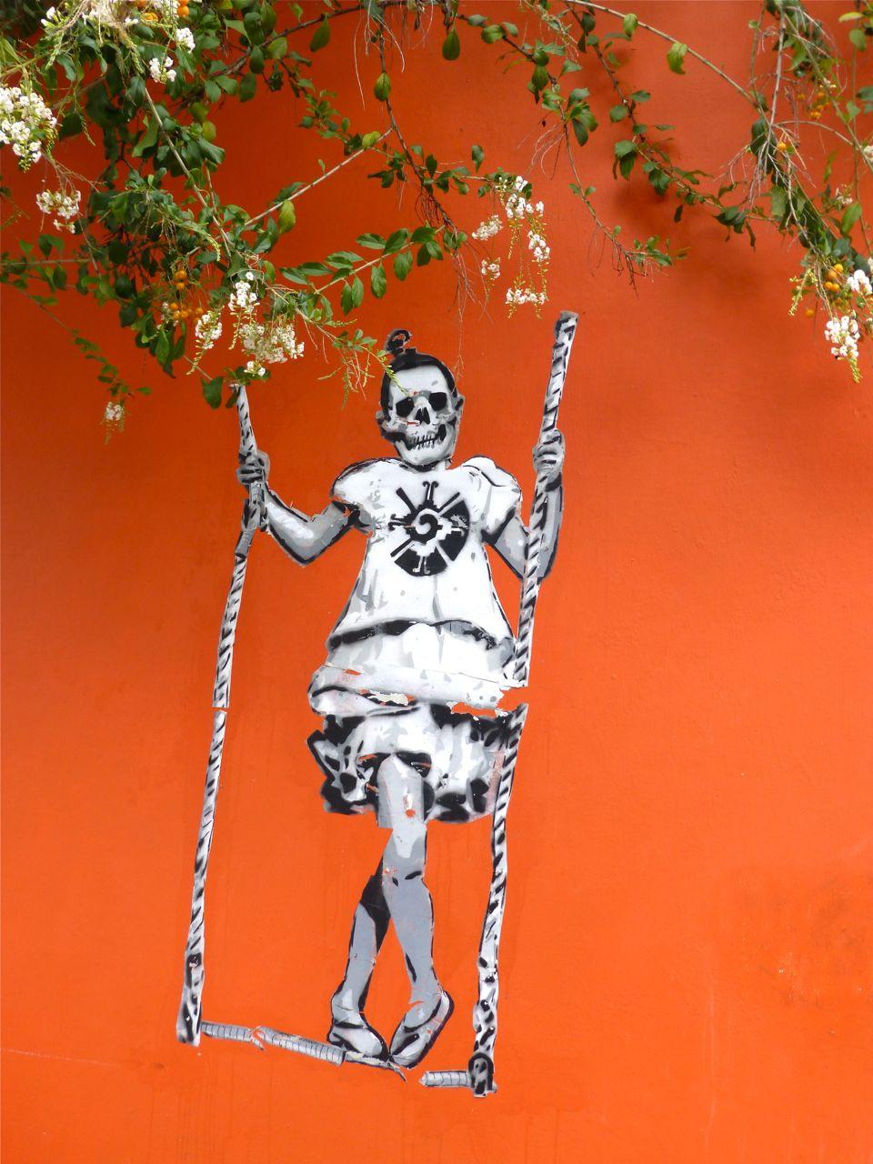 Skeleton on swing painted on orange wall