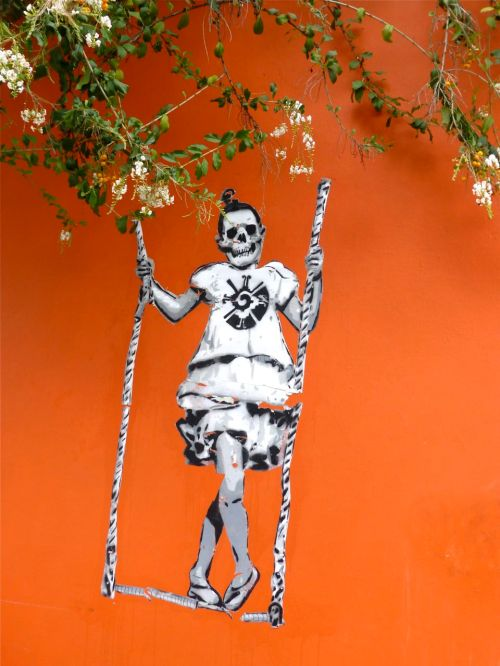 Skeleton on swing painted on orange wall