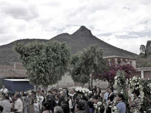 Mourners in church plaza, El Picacho in background