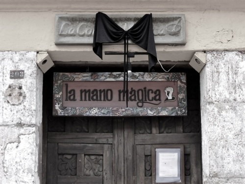 Black bow above closed doors of La Mano Mágica
