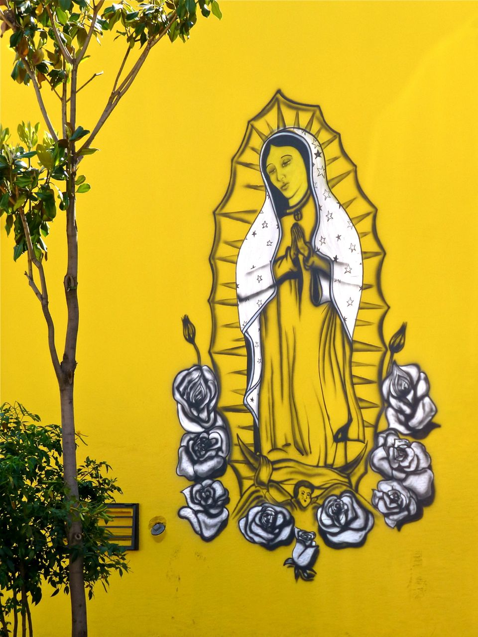 Virgin of Guadalupe painted on yellow wall