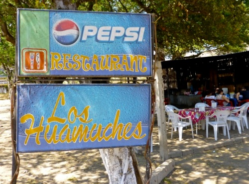 Sign for Los Huamuches with tables in background