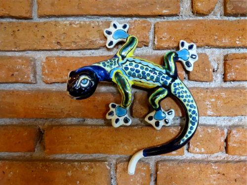 Blue, green, yellow and white ceramic gecko on brick wall.