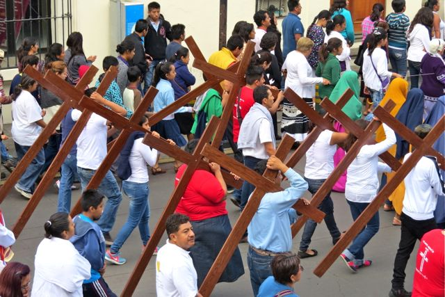 People dragging wooden crosses