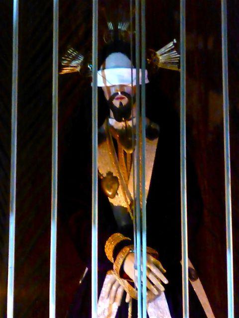Blindfolded statue of Jesus behind bars