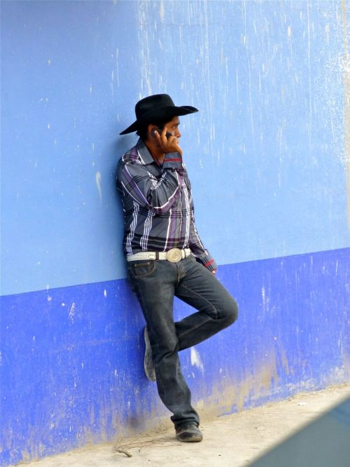 Young man leaning against blue wall talking on cell phone