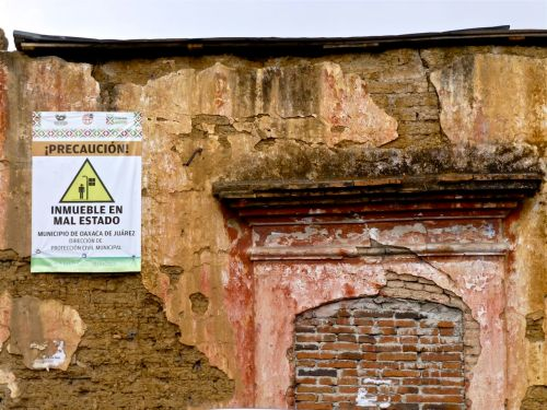 "crumbling adobe wall with sign ""precaución! inmueble en mal estado"""