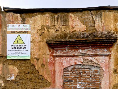 """crumbling adobe wall with sign """"precaución! inmueble en mal estado"""""""